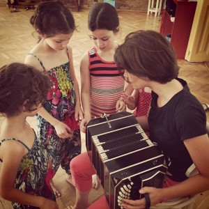 Children are observing the bandoneón in a tango course at BTC